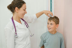 Doctor measures growth boy in medical office Stock Images