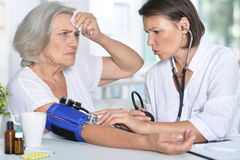 Doctor measures the pressure her senior patient Royalty Free Stock Images