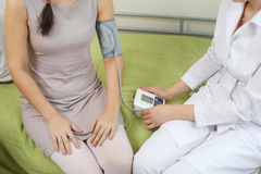 Doctor measures pressure to a woman. Close-up, real clinic Stock Photos