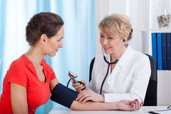 The doctor measures the pressure of woman. The doctor measures the pressure of a young woman Stock Photography
