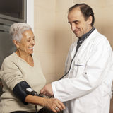 Doctor measuring blood pressure. Male doctor measuring blood pressure of senior patient at hospital Royalty Free Stock Photo