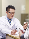 Doctor measuring blood pressure Stock Photos
