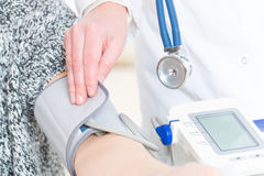 Doctor measuring blood pressure Stock Image