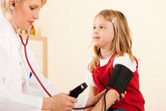 Doctor measuring blood pressure of child. Female doctor measuring blood pressure of a child patient using the pressure sleeve and her stethoscope Royalty Free Stock Images