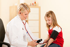 Doctor measuring blood pressure of child. Female doctor measuring blood pressure of a child patient using the pressure sleeve and her stethoscope Stock Photos