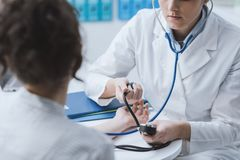 Doctor measuring blood pressure royalty free stock images