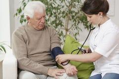 Doctor measuring blood pressure. Of elder man Royalty Free Stock Images