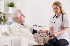 Doctor measuring blood pressure Stock Photography