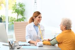 Doctor measuring blood pressure of elderly patient royalty free stock images