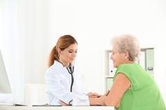 Doctor measuring blood pressure of elderly patient royalty free stock image