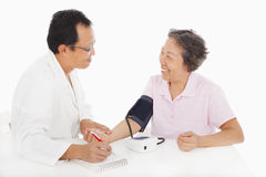 Doctor measuring blood pressure of female patient Stock Photos