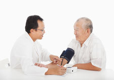Doctor measuring blood pressure of male patient Stock Photo