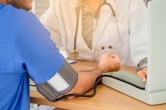 Doctor measuring blood pressure of male patient royalty free stock photography