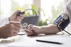 Free Doctor Measuring Blood Pressure Of Patient Stock Photography - 142599152