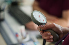 Doctor measuring blood pressure of a patient. Blood pressure gage in a doctor`s hands Stock Photo
