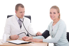 Doctor measuring blood pressure of patient in office isolated on Stock Photo