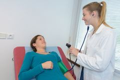 Doctor measuring blood pressure pregnant woman in clinic Royalty Free Stock Images