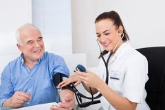 Doctor measuring blood pressure of senior man. Happy female doctor measuring blood pressure of senior men in clinic Stock Photography