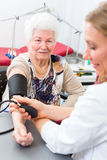 Doctor measuring blood pressure of senior patient. Young female doctor measuring blood pressure of senior patient in surgery consultation hour Royalty Free Stock Image