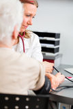 Doctor measuring blood pressure of senior patient Royalty Free Stock Photos