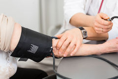 Doctor measuring blood pressure of senior patient. Young female doctor measuring blood pressure of senior patient in surgery consultation hour Royalty Free Stock Photo