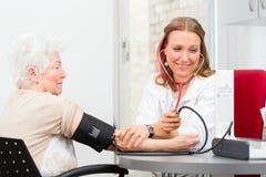 Doctor measuring blood pressure of senior patient Stock Image