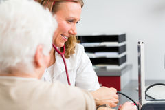 Doctor measuring blood pressure of senior patient Royalty Free Stock Images