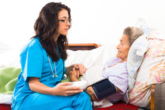 Doctor Measuring Blood Pressure. Doctor measuring senior patients blood pressure Royalty Free Stock Photography
