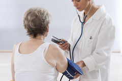 Doctor measuring blood pressure of senior woman Stock Image