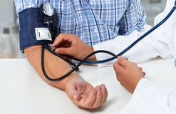 Doctor measuring blood pressure with sphygmomanometer. Doctor checking old man blood pressure. Health care background Royalty Free Stock Photo