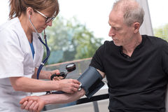 Doctor measuring blood pressure with sphygmomanometer. Female doctor measuring blood pressure with sphygmomanometer royalty free stock photos