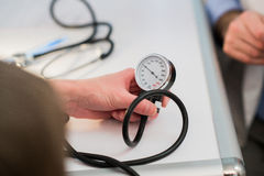 Doctor is measuring blood pressure with a tonometer Royalty Free Stock Image