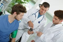 Doctor measuring blood pressure young patient Stock Image