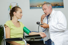 Doctor measuring blood pressure young woman Royalty Free Stock Photography