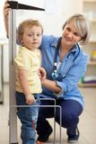 Doctor measuring boy`s height Stock Photo