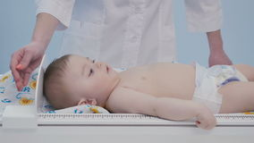 The doctor measuring the growth of a child. Cute baby lays on the table on nappy. The doctor measuring the growth of a child. Adorable boy moves hands and legs stock video