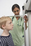 Doctor Measuring Height Of A Boy Stock Images