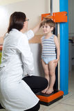 Doctor Measuring Height of Little Boy on Traditional Medical Scale Royalty Free Stock Image
