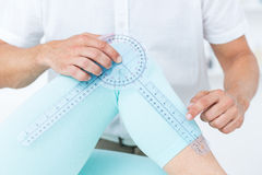 Doctor measuring knee with goniometer Stock Image
