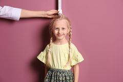 Doctor measuring little girl`s height. On color background stock images