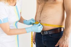 Doctor measuring man`s body fat royalty free stock photos