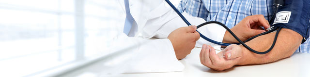 Doctor measuring patient blood pressure. Royalty Free Stock Photos
