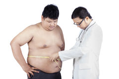 Doctor measuring a patient obesity 1. Doctor examining a patient obesity, shot in hospital Royalty Free Stock Photography