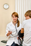 Doctor measuring patient's blood pressure Royalty Free Stock Photo