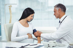 Doctor measuring pressure of pregnant woman stock image