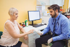 Doctor measuring sugar level of patient with glucometer stock photography