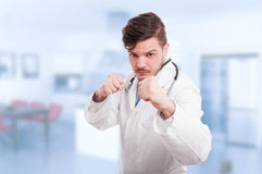 Doctor or medic acting violent. And being ready to fight holding his fists up Royalty Free Stock Photos