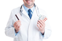 Doctor or medic holding pills blisters and credit card Stock Image