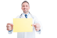 Doctor or medic holding yellow blank paper with copy space Stock Photo