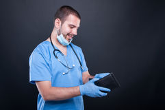 Doctor or medic looking in his wallet and smiling Royalty Free Stock Image